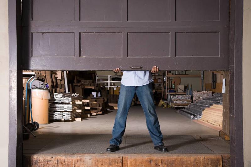 a guy lifting a heavy garage door
