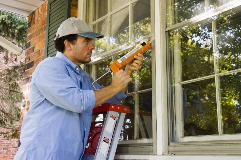 a man caulking his windows